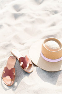 sandals and hat on sandy beach